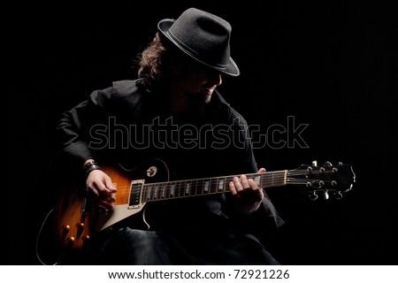 Guitarist in black hat playing guitar - stock photo