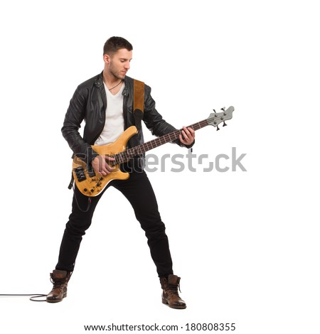 Guitarist in black leather jacket plays the bass guitar. Full length studio shot isolated on white. - stock photo