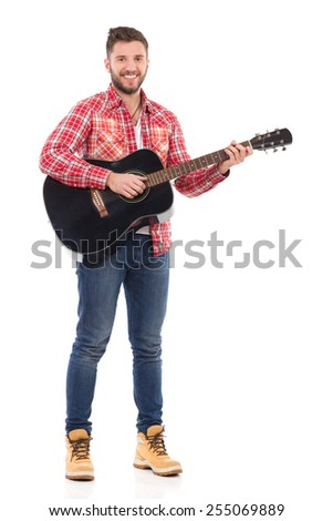 Guitarist in red lumberjack shirt posing with the black acoustic guitar. Full length studio shot isolated on white. - stock photo