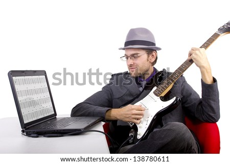 Guitarist looking at tablature online.  Isolated on a white background. - stock photo