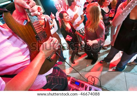 Guitarist maxing out on his guitar with a large group of people on the dance floor in a nightclub - stock photo