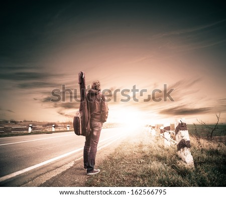guitarist on a road to horizon - stock photo