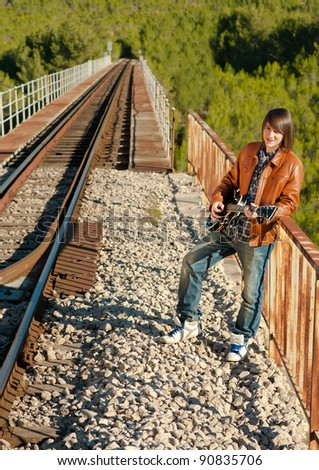 Guitarist performing on a railway bridge - stock photo