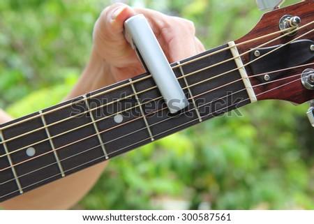 guitarist pin capo to the guitar - stock photo