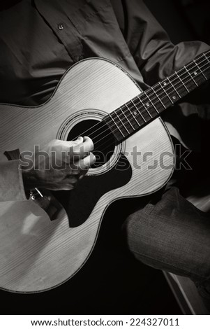 Guitarist playing acoustic guitar. Unplugged performance. - stock photo