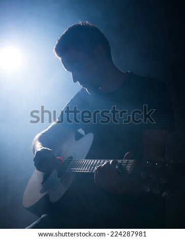 Guitarist playing acoustic guitar. Unplugged performance in the dark. - stock photo