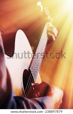 Guitarist playing on acoustic guitar in front of the light - stock photo
