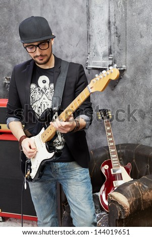 Guitarist plays guitar in room powdered with snow and with scuffed walls - stock photo