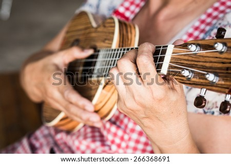 guitarist plays, Ukulele plays : soft focus on left hand finger. - stock photo