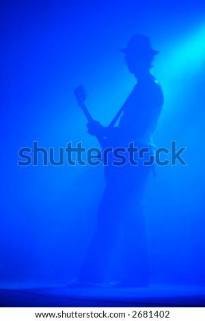 Guitarist shrouded in blue light - stock photo