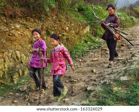 GUIZHOU PROVINCE, CHINA - APRIL 11: Chinese family descends rocky mountain path, two girls are 8 years old, and their mother, farmer, peasant, holding bundle of firewood in his hands, April 11, 2010.
