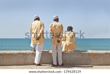GUJARAT, INDIA - FEBRUARY, 27: Traditional dressed Hindu clerics standing / squatting on perimeter to promenade at Arabian Sea watching patiently on February 27, 2013 in Dwarka, Gujarat, India