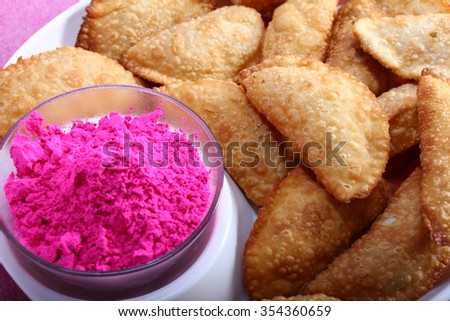 Gujias, the traditional indian snack for holi festival with pink color in bowl