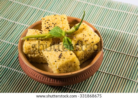 Gujrati khaman Dhokla in terracotta bowl, isolated over green ken mat