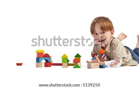 Gulliver in the Country of Lilliputs. Cute 3-years old boy and small town build from wooden blocks. Isolated on white background. - stock photo