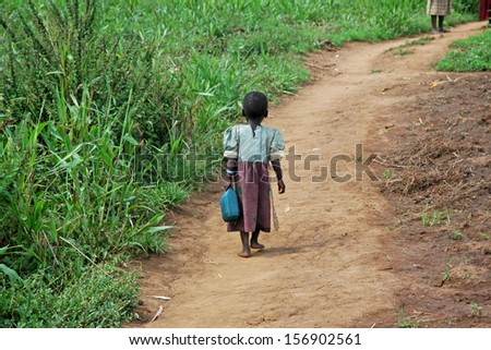 GULU, UGANDA, AFRICA - CIRCA MAY 2005:  Unidentified little girl carries a blue jerry-can down a dirt path circa May 2005 in Uganda, Africa. - stock photo