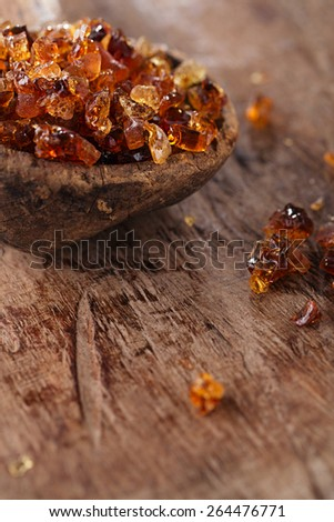 Gum arabic, also known as acacia gum - in old wooden spoon - stock photo