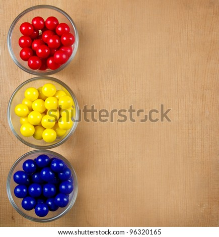Gumballs in three colors, the primary colors red, yellow and blue with a wooden background for copy space. - stock photo