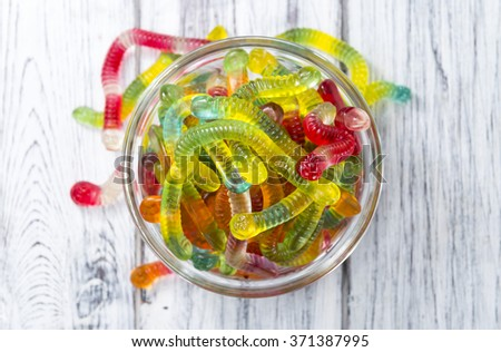 Gummi Candy (worms) on wooden background (selective focus) - stock photo
