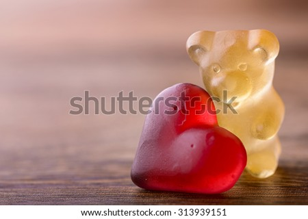 gummy bear with red heart on wood for valentines - stock photo