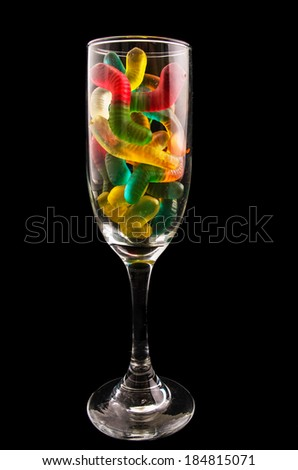 gummy bears  and a wine glass on a dark background - stock photo