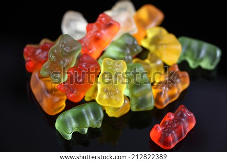 Gummy bears on a black background. - stock photo