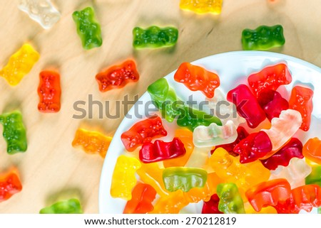 gummy bears on a white plate and wooden table - stock photo