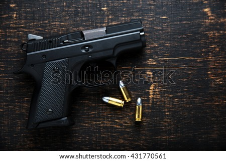 Gun and ammunition on dark wooden table. top view - stock photo