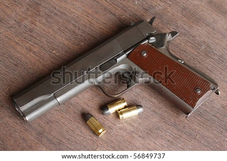Gun and bullets on a table - stock photo
