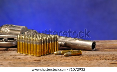 Gun and bullets on old vintage wood table with copy space - stock photo