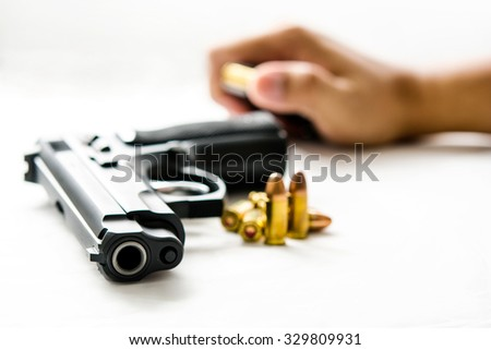 Gun and group of Bullets or ammunition on white  background,Selective  focused on the front of the gun and blur picture style - stock photo