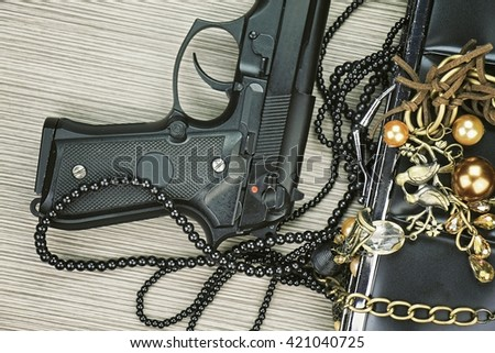 Gun and purse, Woman bag with gun, Woman's clutch purse with gun and accessories, Handgun and accessories falling from a woman's purse. (Color Process) - stock photo