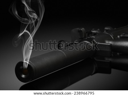 gun barrel with smoke on black background. Soft focus - stock photo