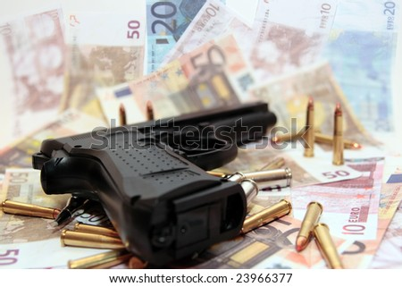 gun bullets and money showing a dangerous side to life - stock photo
