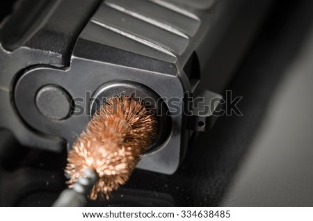 Gun Cleaning - Brush Cleaning Barrel of Firearm - stock photo