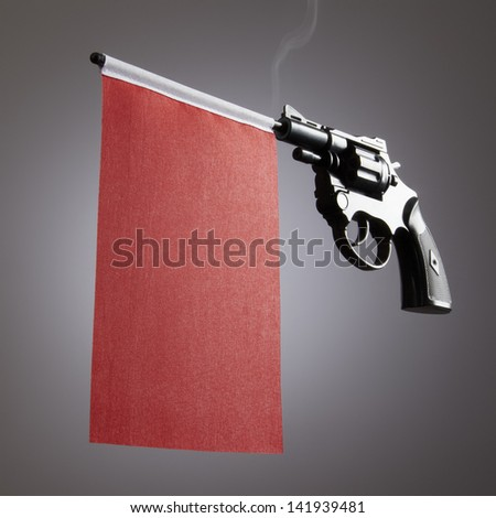 Gun crime concept of hand pistol showing a blank red flag - stock photo