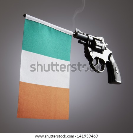 Gun crime concept of hand pistol showing the flag of ireland - stock photo