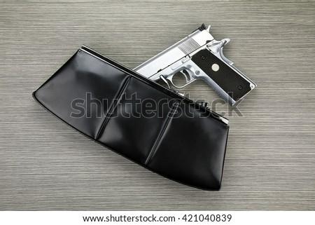 Gun in a purse, Woman bag with gun hidden, Woman's clutch purse with gun, Handgun falling from a woman's purse. - stock photo