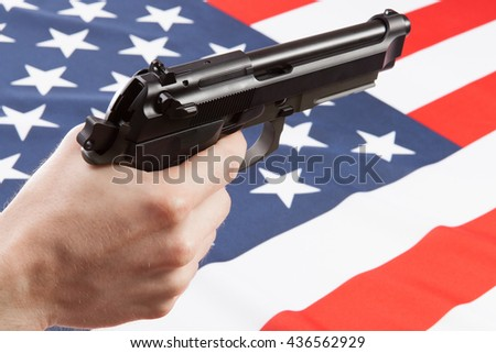 Gun in hand with ruffled national flag on background - USA - stock photo