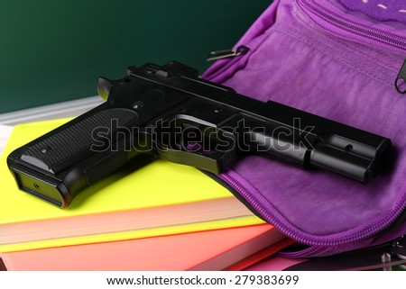 Gun in school backpack close-up, on blackboard background - stock photo
