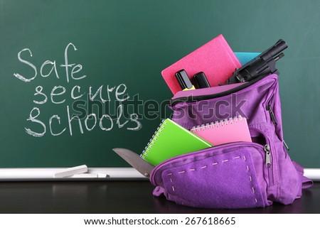 Gun in school backpack on wooden desk, on blackboard background - stock photo