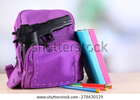 Gun in school backpack on wooden table, on bright background - stock photo