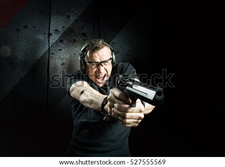 Gun in the hands of the angry man in a headphones
