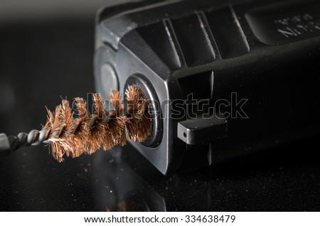 Gun Maintenance - Brush Cleaning Bore of Firearm - stock photo