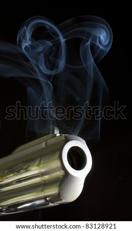 gun moving and belching smoke as a bullet leaves - stock photo