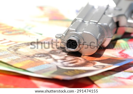 Gun muzzle on a pile of new Israeli Shekels (NIS) banknotes  - stock photo