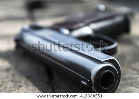 Gun on a wooden table - stock photo