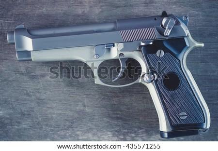 Gun on wooden background.Selective focus. - stock photo
