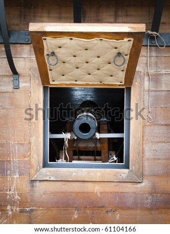 Gun port of an eighteenth century galleon open and with a cannon in place. Looking straight down the cannon's throat - stock photo