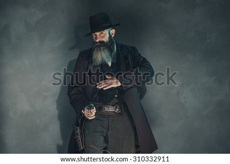 Gun shooting vintage crook with long beard in 1900 style clothing against grey wall. - stock photo